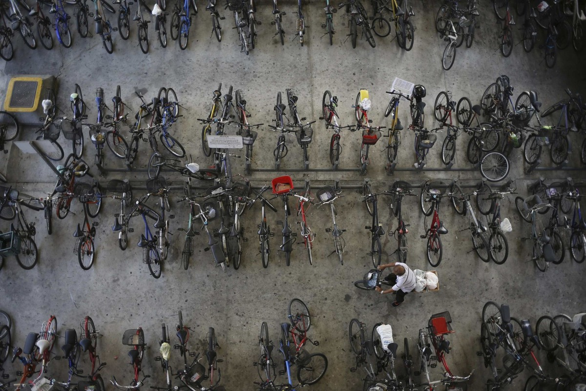 Image: A man rides off with his bicycle outside a train station in Singapore