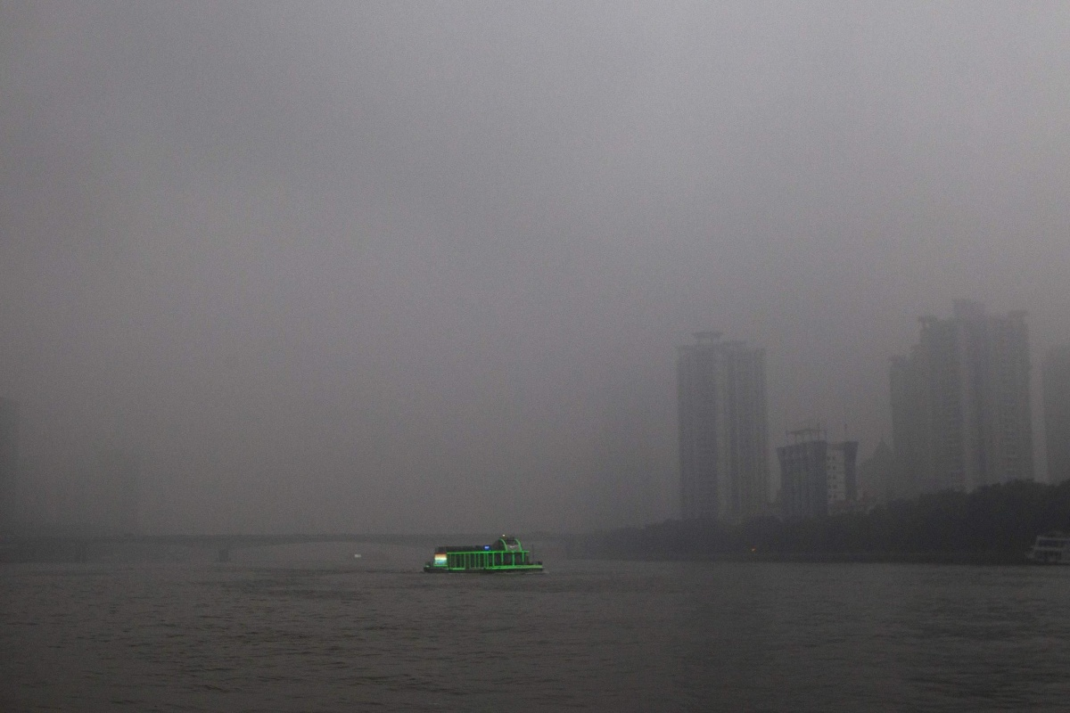 Image: A tourist boat, decorated with green lights, travels on the Pearl River amid heavy haze in Guangzhou.