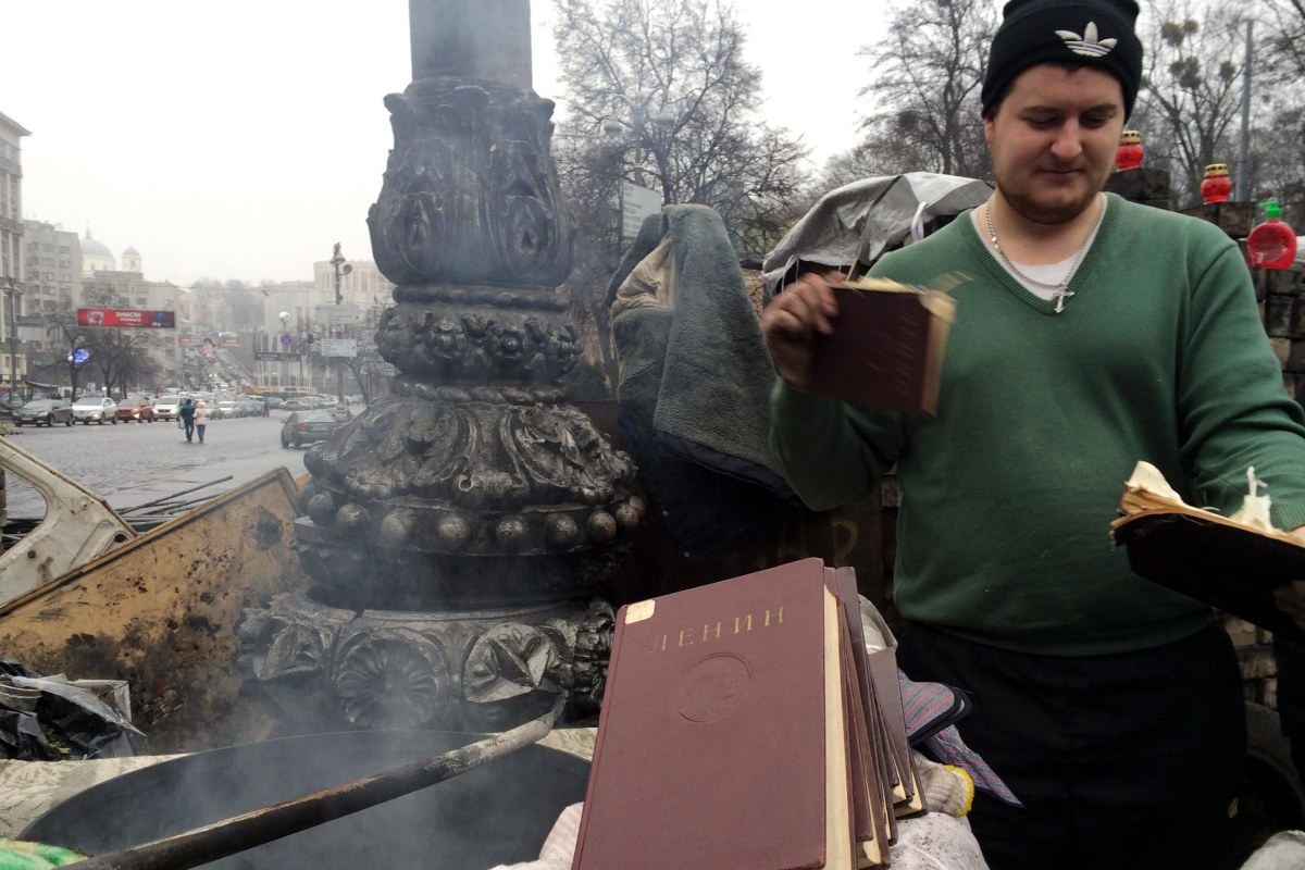 A protester in Kiev burning books by Vladimir Lenin.