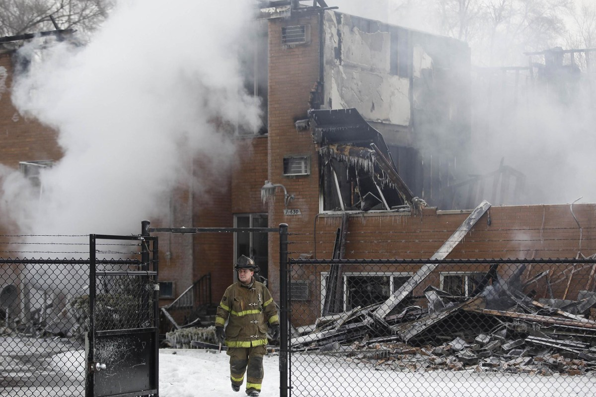Image: A fireman walks away from an apartment building after it was destroyed by a four-alarm blaze on Detroit's west side early