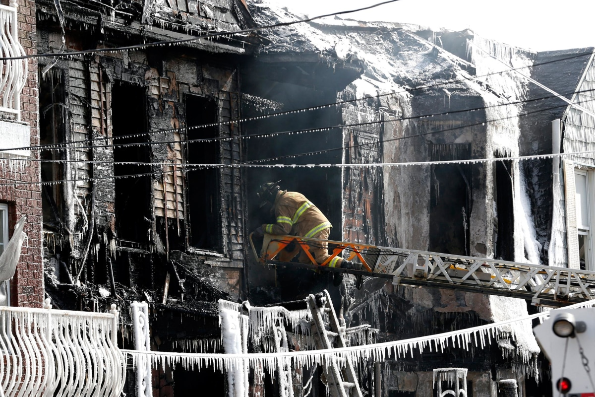 Image: A firefighter inspects a charred home while standing on a ladder from a fire truck in Jersey City, N.J.