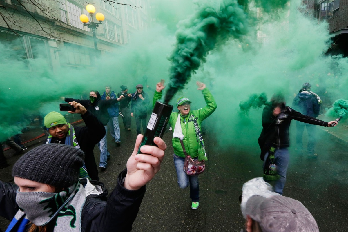 "Image: Members of the Emerald City Supporters and other fan groups burn smoke devices as they take part in the traditional ""March to the Match"" before the Seattle Sounders season-opening MLS soccer match"