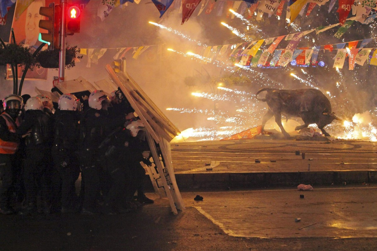 Image: Riot policemen shield themselves as fireworks thrown by protesters explode next to the statue of a bull, during an anti-government protest in Kadikoy