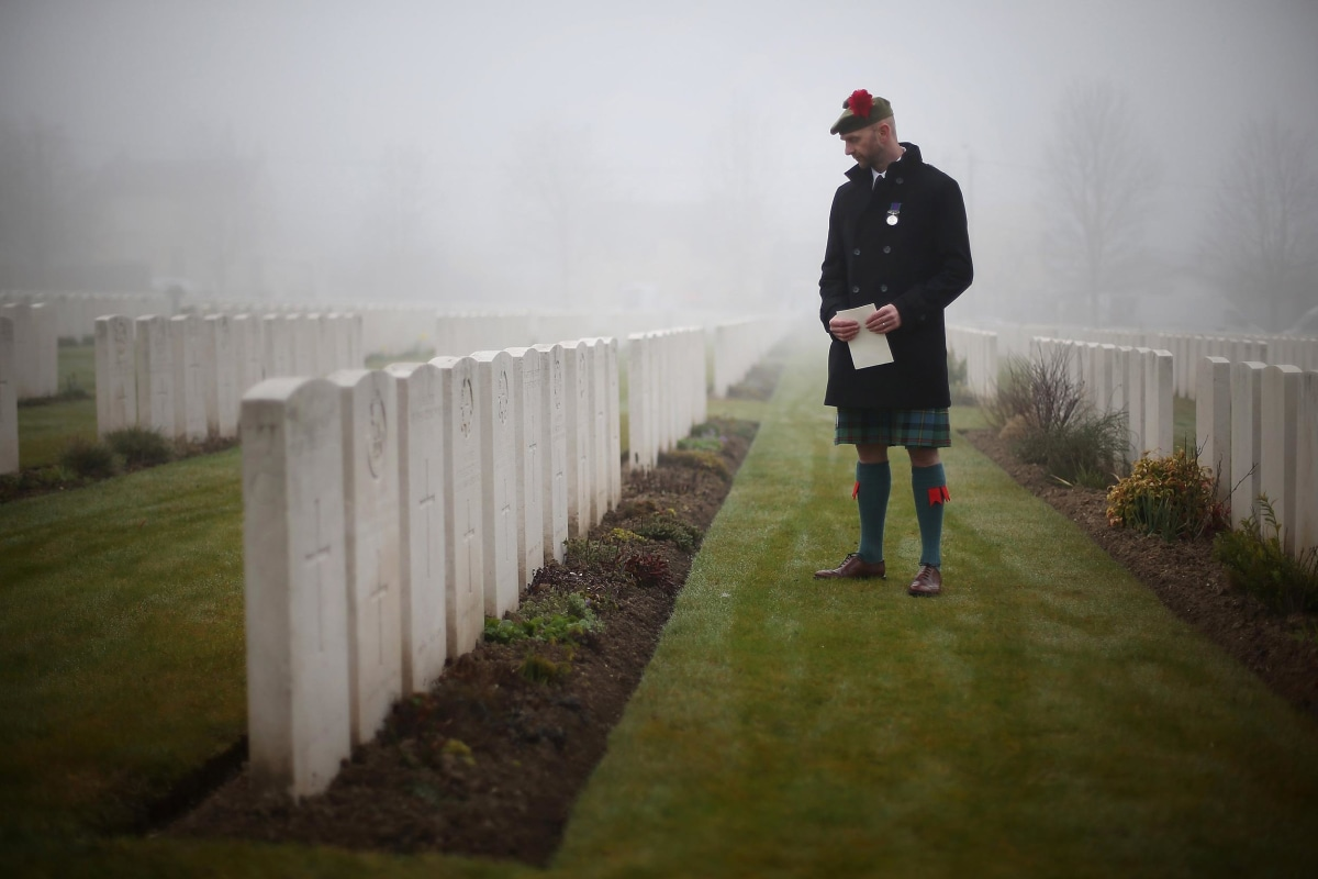 Image: Stephen McLeod, great step nephew of World War One soldier Private William McAleer, looks at headstones before a reburial ceremony at Loos British Cemetery