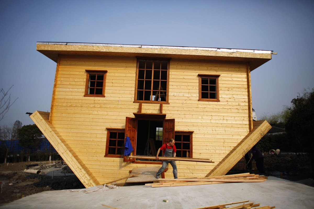 Image: A laborer works at an upside-down house under construction