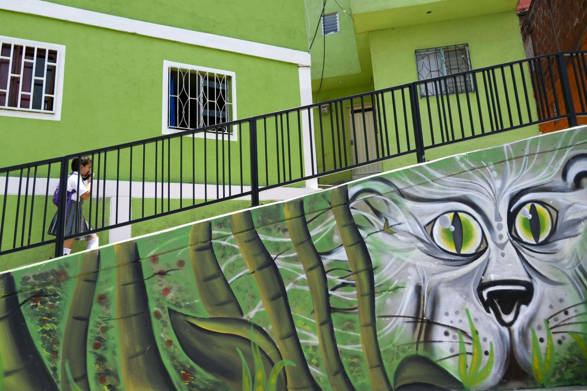 Image: A students walks past a mural, part of the project 'Medellin is painted for life,' at Comuna 13  in Medellin