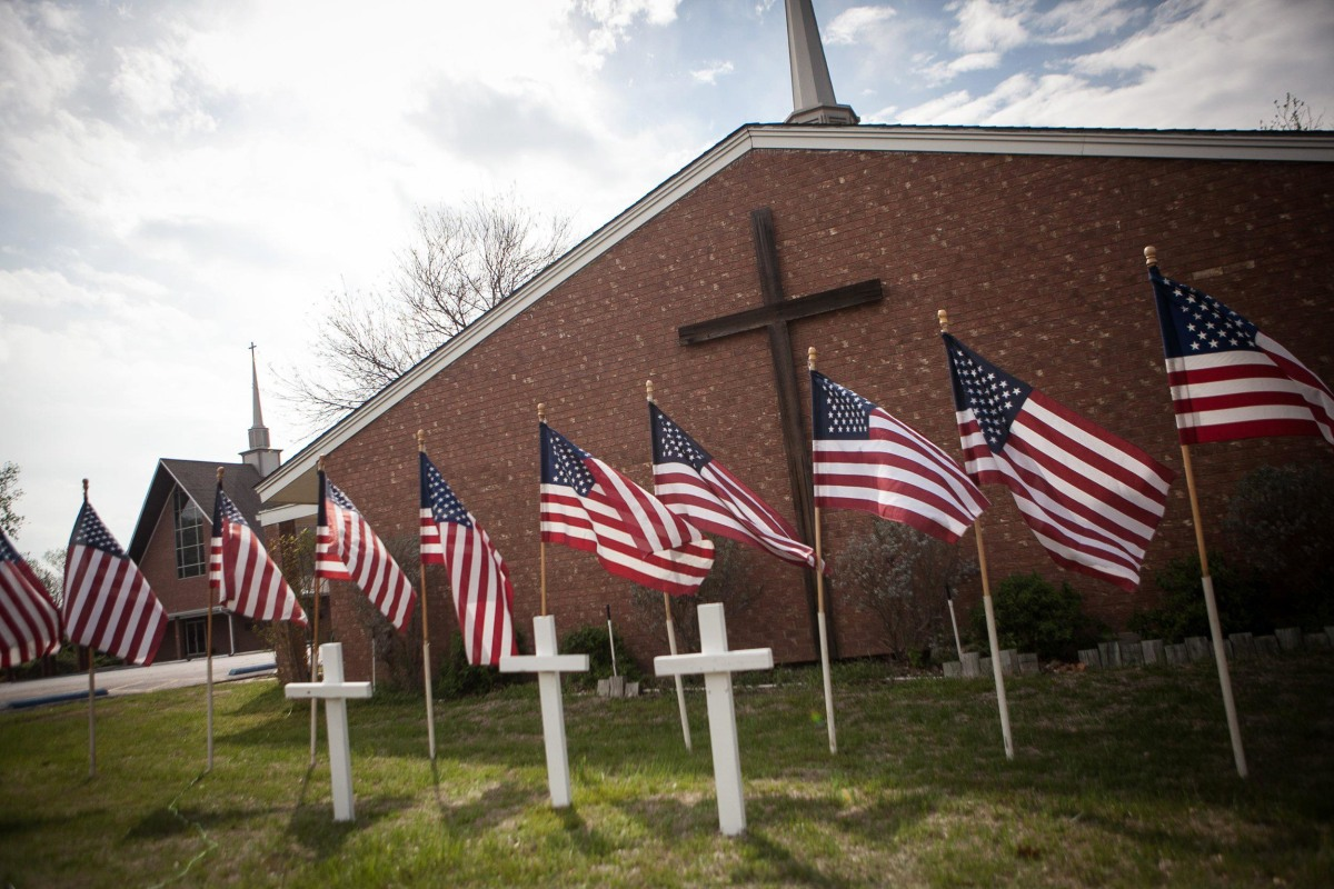 Image: A memorial of three white crosses and 16 flags stands at the Central Christian Church