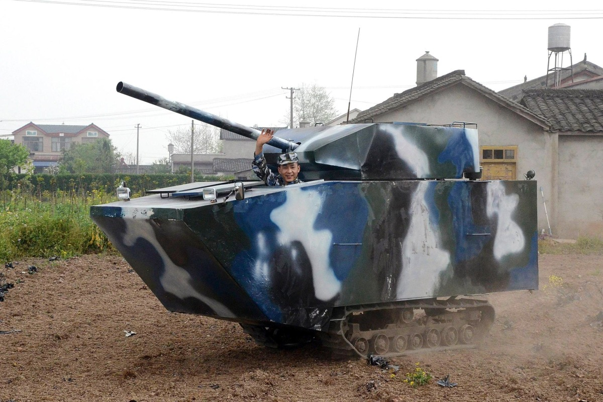 Image: Jian lin waves in his home-made replica of a tank during a trial run, at a village in Mianzhu