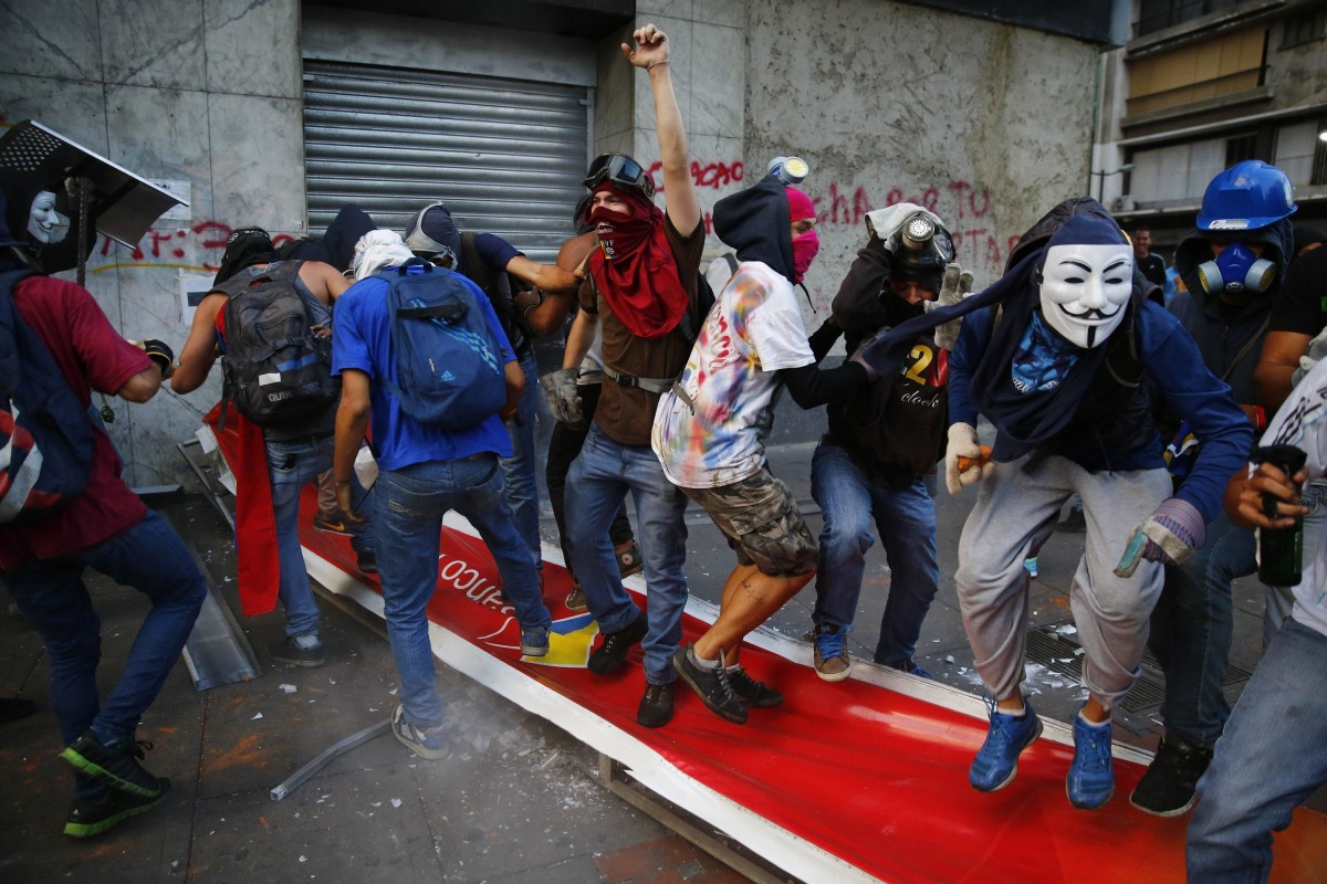 Image: Anti-government protesters jump and step on a banner of Banco de Venezuela after bringing down the banner during riots in Caracas