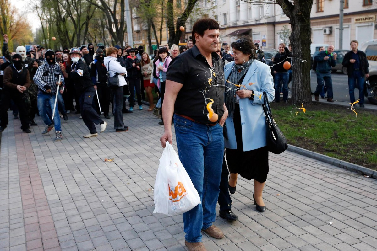 Image: Masked pro-Russia protesters pelt supporters of Yulia Tymoshenko with eggs outside a regional government building in Donetsk