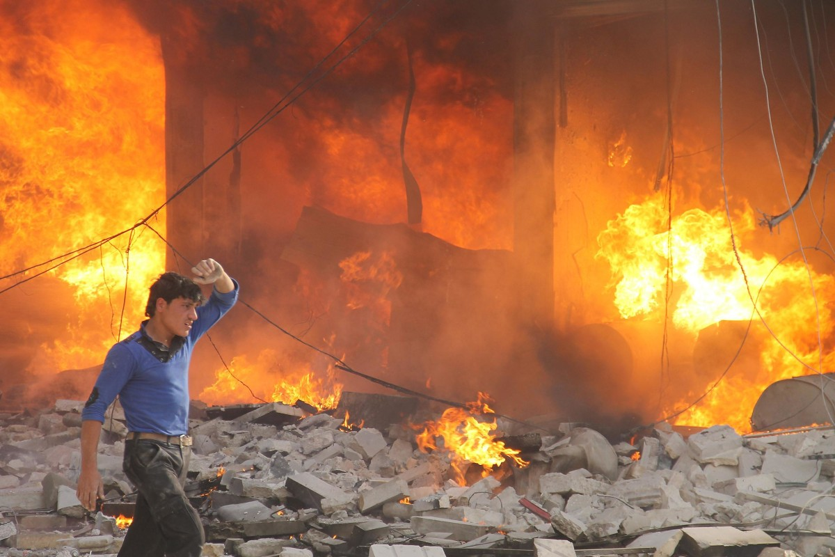 Image: A man walks past a burning building following a reported air strike by pro-regime forces on the northern Syrian city of Aleppo