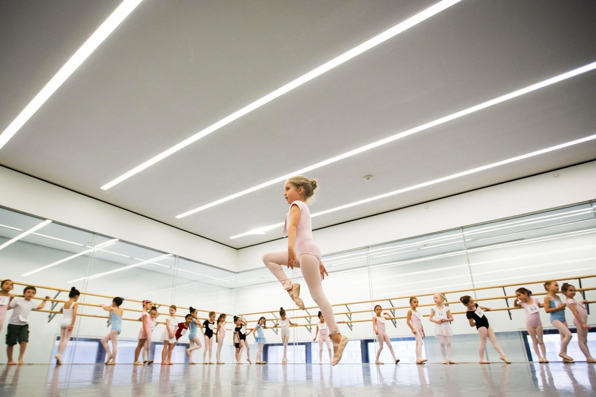 Image: Children watch as a girl dances during an audition for the School of American Ballet in New York
