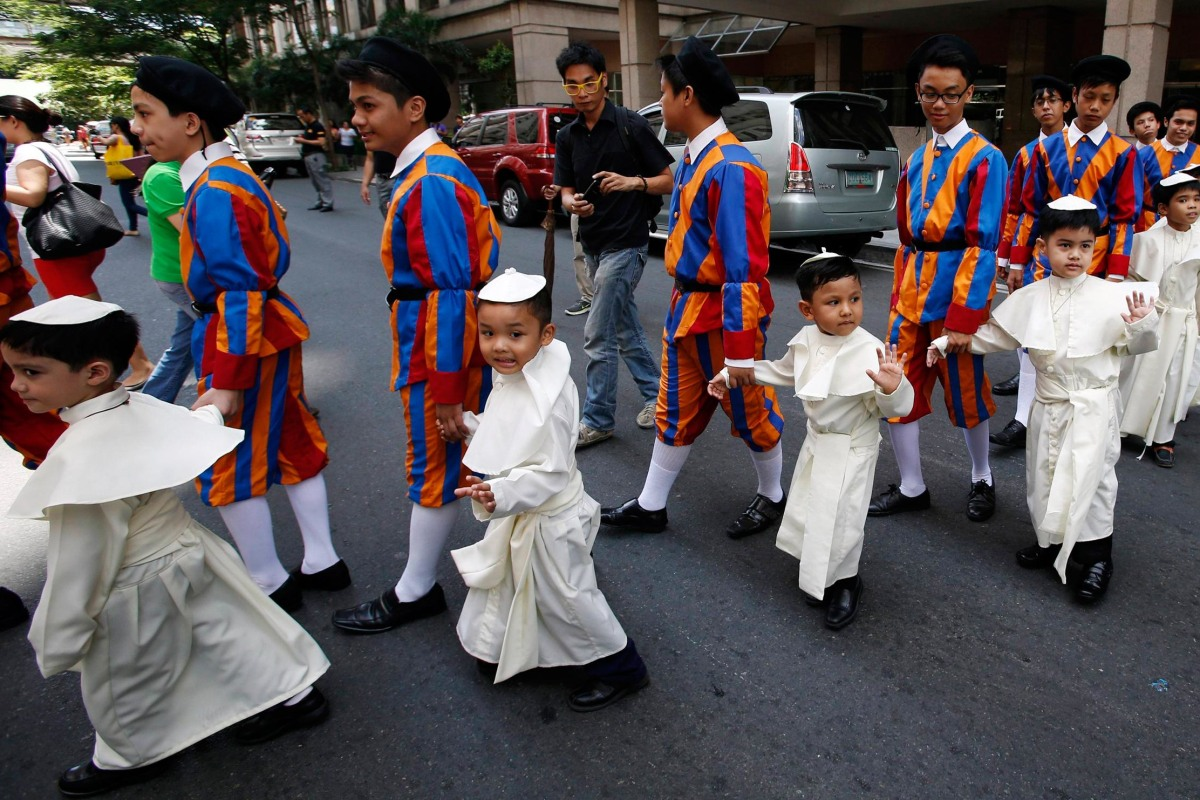 Image: Children wearing Pope's cassocks cross a road before taking part in a parade in Quezon city