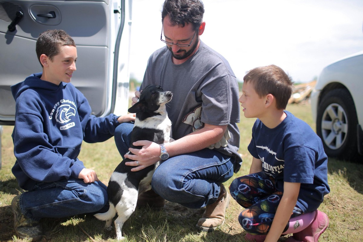 Image: Wade Lentz and his sons Matthew and Landon pet their dog Oreo, who turned up at their house 36 hours after a tornado destroyed their home