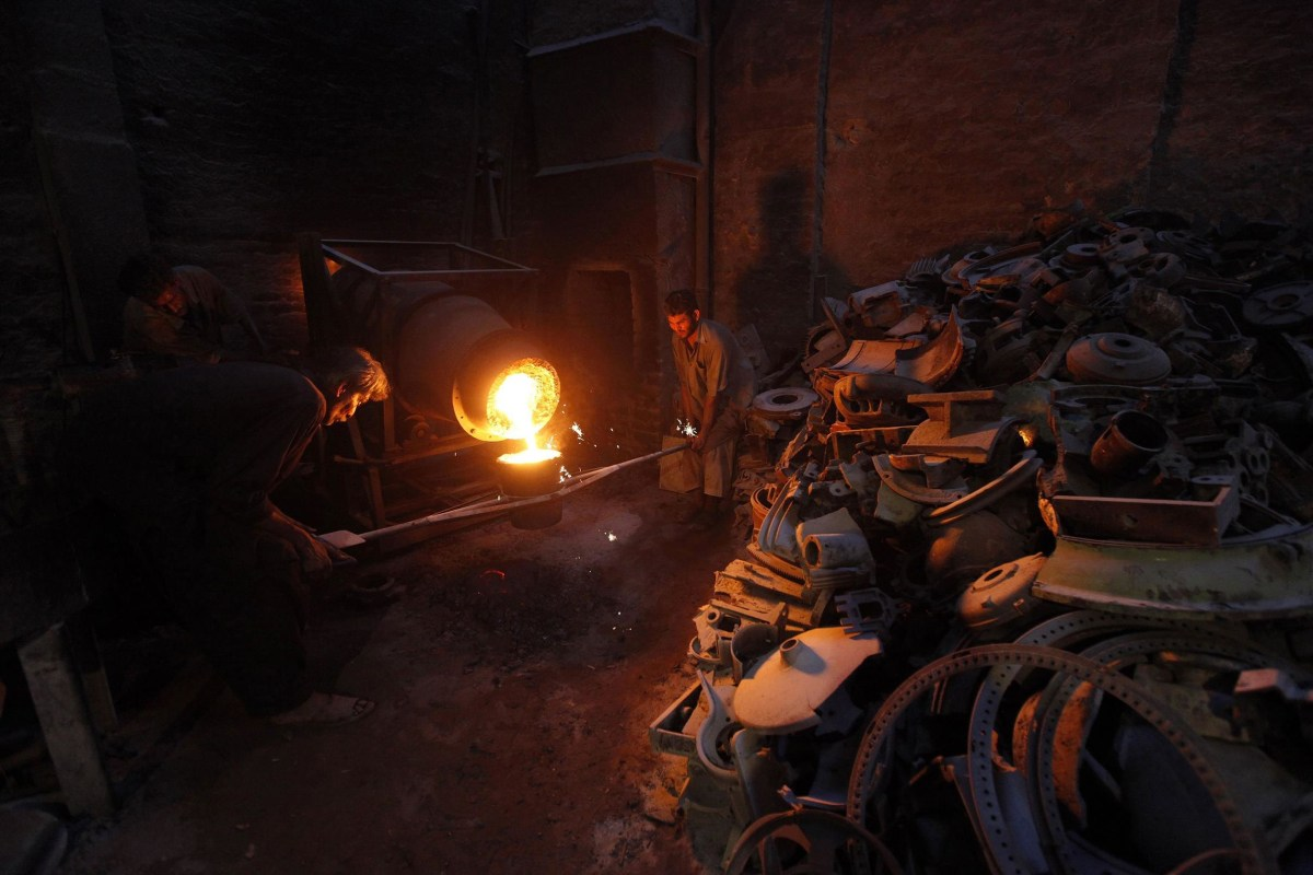 Image: Labourers fill a pot with melted iron to pour into a casting mould to make machine parts in a foundry in Karach