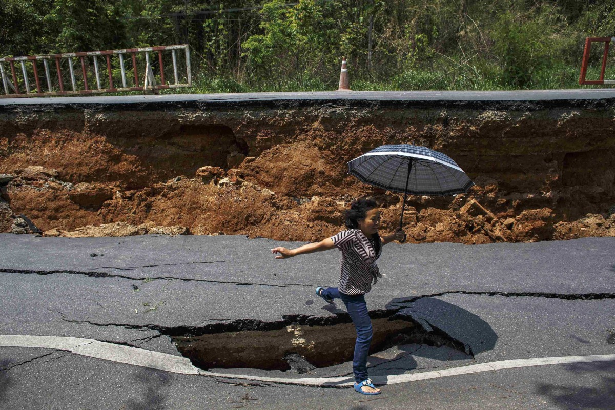 Image: A woman with an umbrella jumps over a hole on a highway road, damaged by Monday's earthquake in Chiang Rai, in northern Thailand