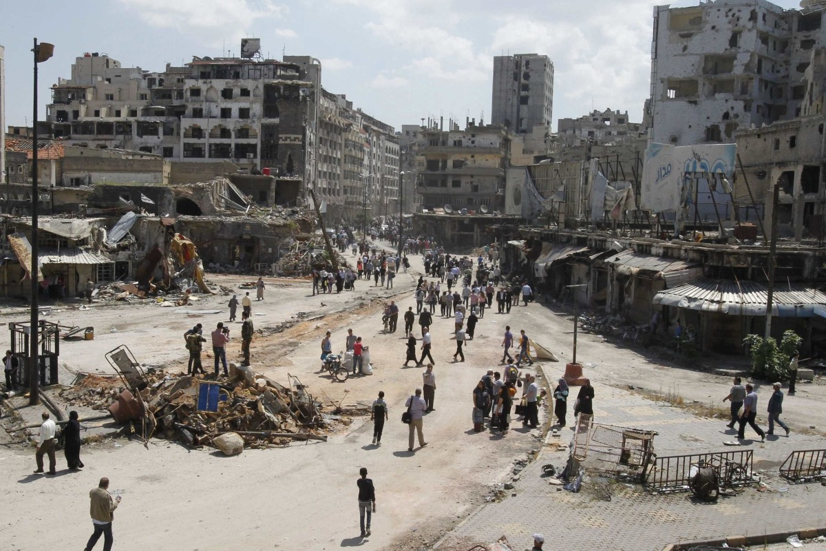 Image: Residents arrive on foot to inspect their homes, after the cessation of fighting between rebels and forces loyal to Syria's President Bashar al-Assad, in Homs city