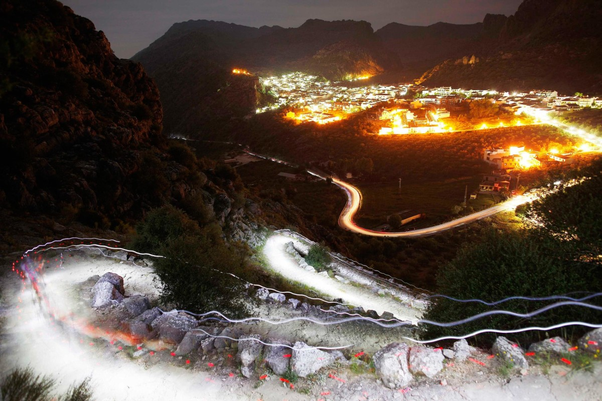 Image: Trails of headlamps are seen as runners make their way to the finish line during the XVII 101km competition on the outskirts of Montejaque