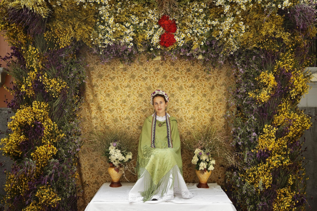 Image: A 'Maya' girl sits on an altar during the traditional celebration of 'Las Mayas' on a street, in central Madrid, Spain