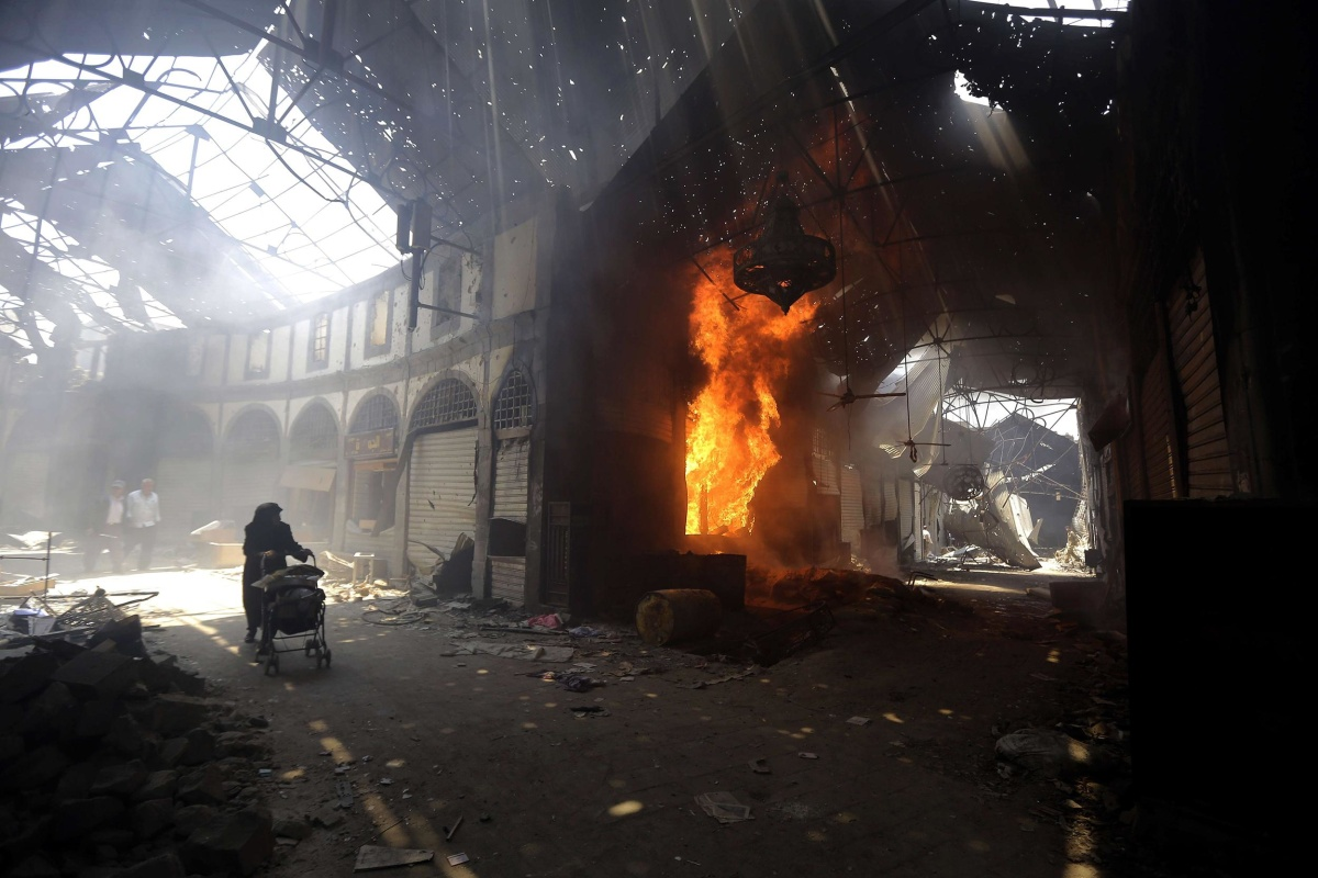 Image: A woman walks past a burning shop in the Maskuf market in the Old City of Homs