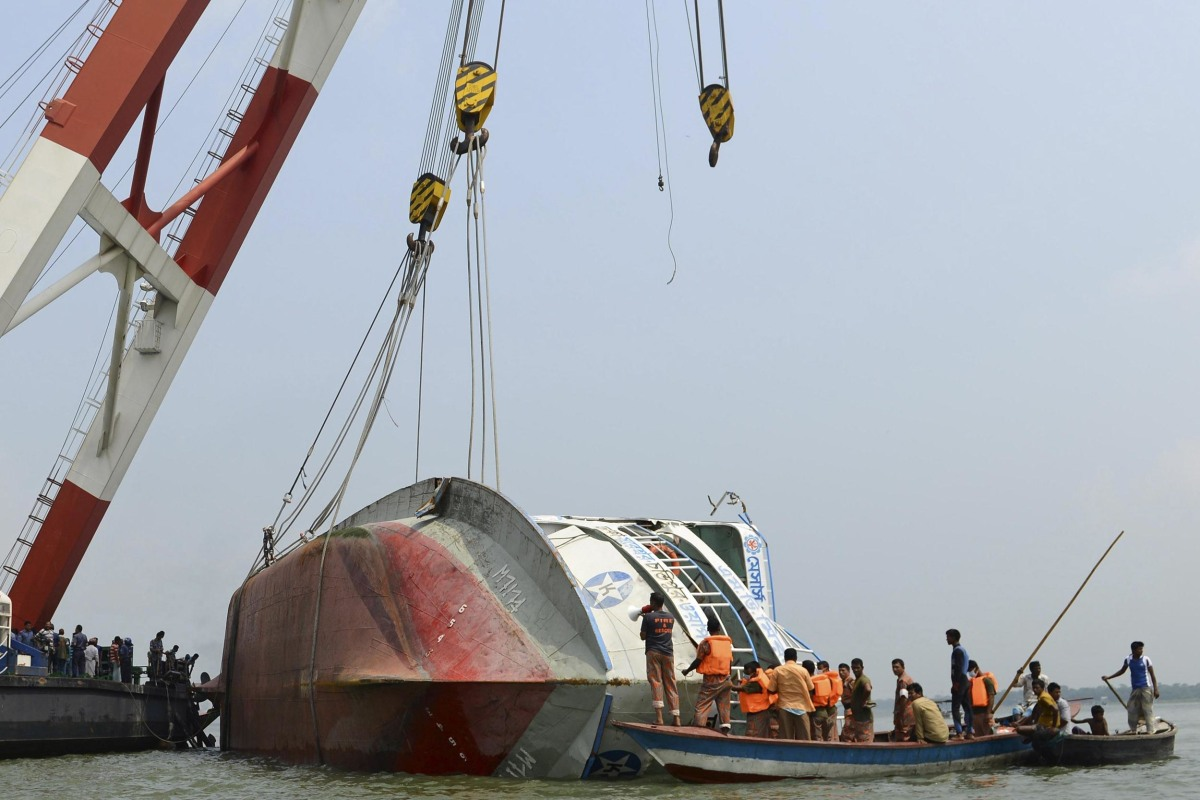 Image: Rescue members inspect the capsized M.V. Miraj 4 ferry during a salvage operation at the Meghna river at Rasulpur in Munshiganj district