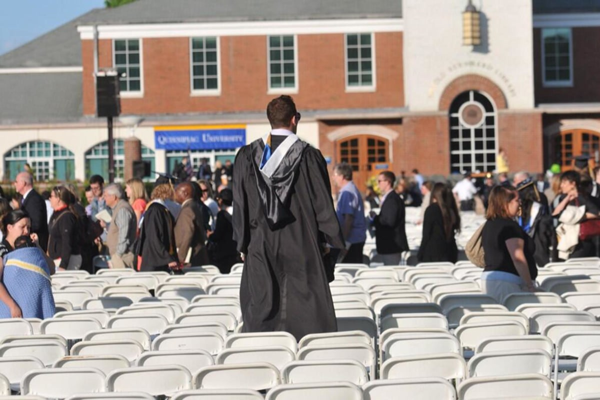 Image: A graduate looks for relatives as people evacuate Quinnipiac University's campus after 'multiple' security threats