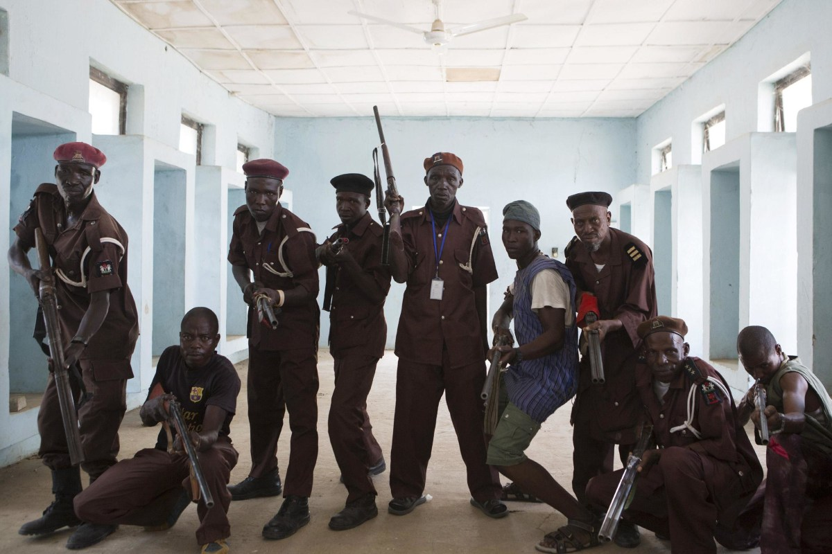 Image: Members of a vigilante group of traditional hunters pose for a picture at their camp in Maiduguri