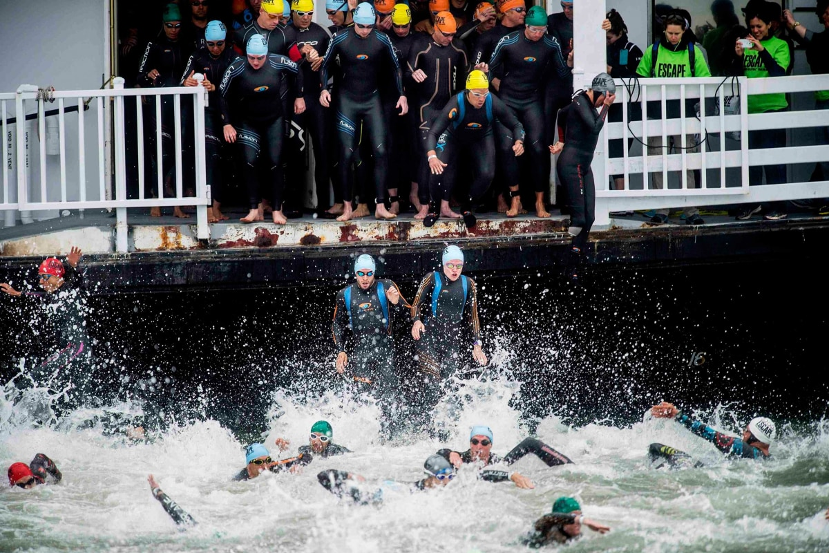Image: Swimmers jump from the San Francisco Belle at the start of the 34th annual Escape from Alcatraz Triathlon in San Francisco