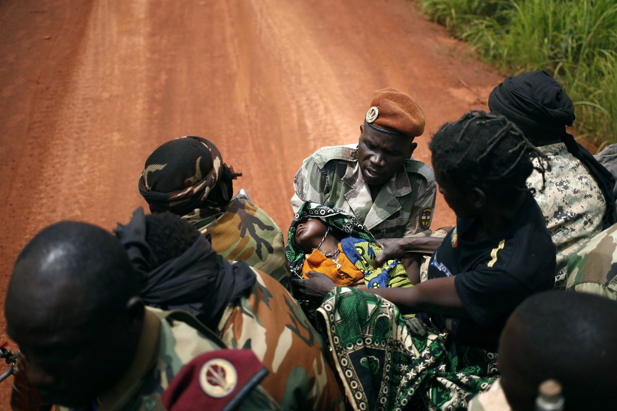 Image: Seleka fighters carry a sick child to her mother, at a village between Bambari and Grimari