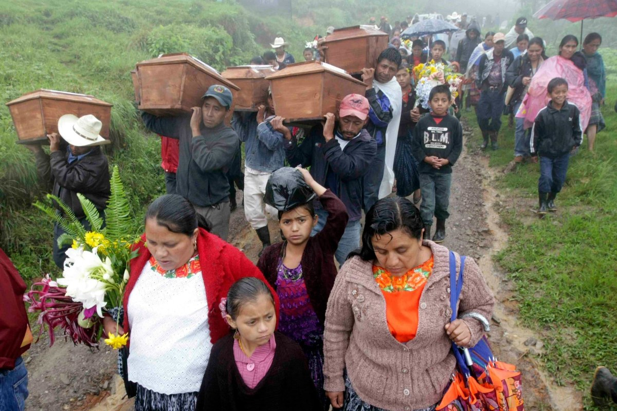 Image: Indigenous people walk with the remains of six people, who had disappeared in 1982 during the Guatemalan Civil War, at Pambach in the Alta Verapaz region