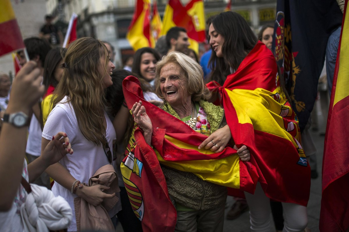 Image: Dozens of demonstrators gather and wave Spanish flags around the monument of Charles III, a former King of Spain, during a demonstration in support of the Spanish Monarchy in the main square of Madrid, Spain
