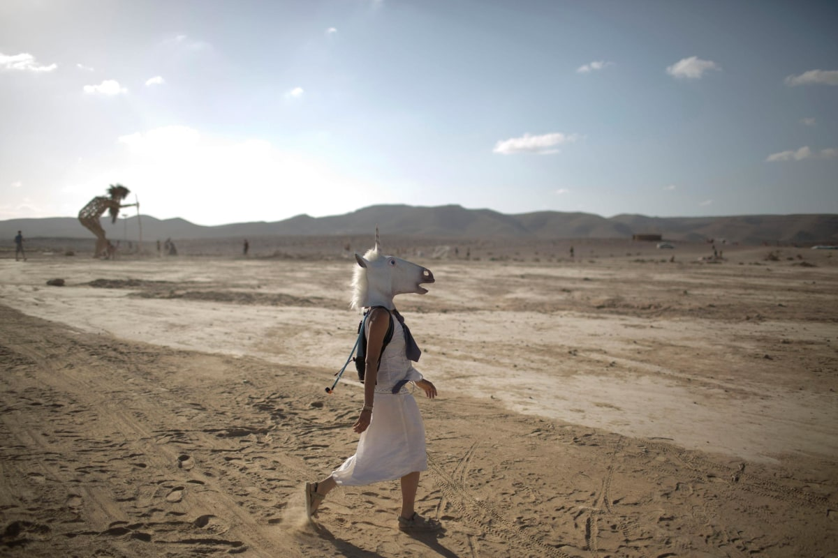 Image: An Israeli woman wears a unicorn mask as she walks in the playa during Israel's first Midburn festival