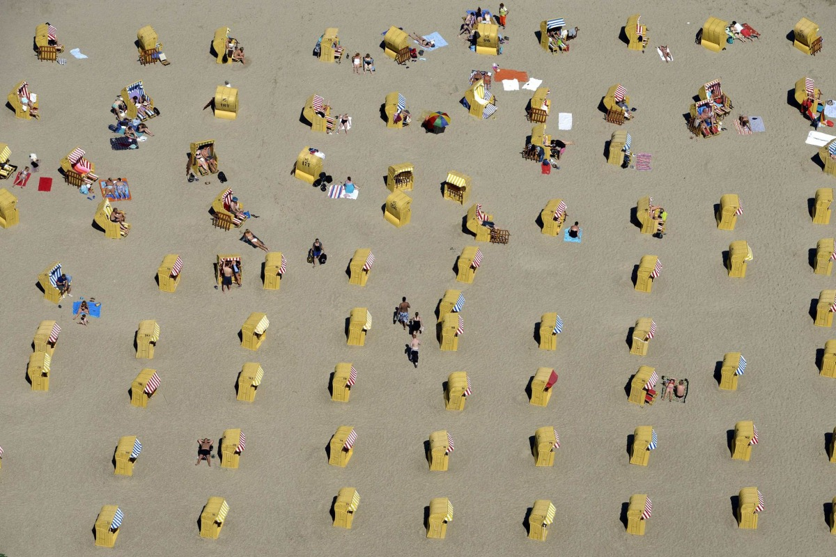 Image: People take a sunbath in their beach chairs at a beach in Travemuende
