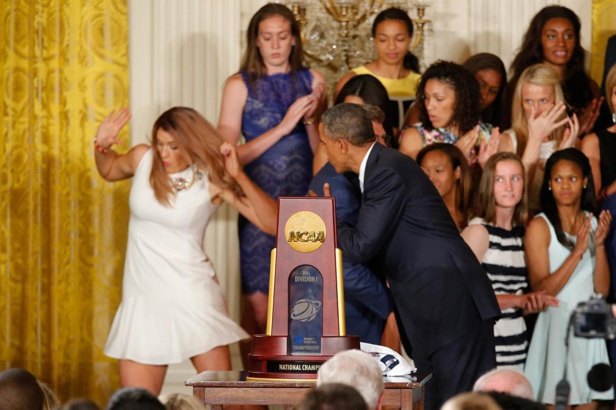 Image: U.S. President Obama hugs UConn women's basketball coach Auriemma as team star Dolson falls off the stage in Washington