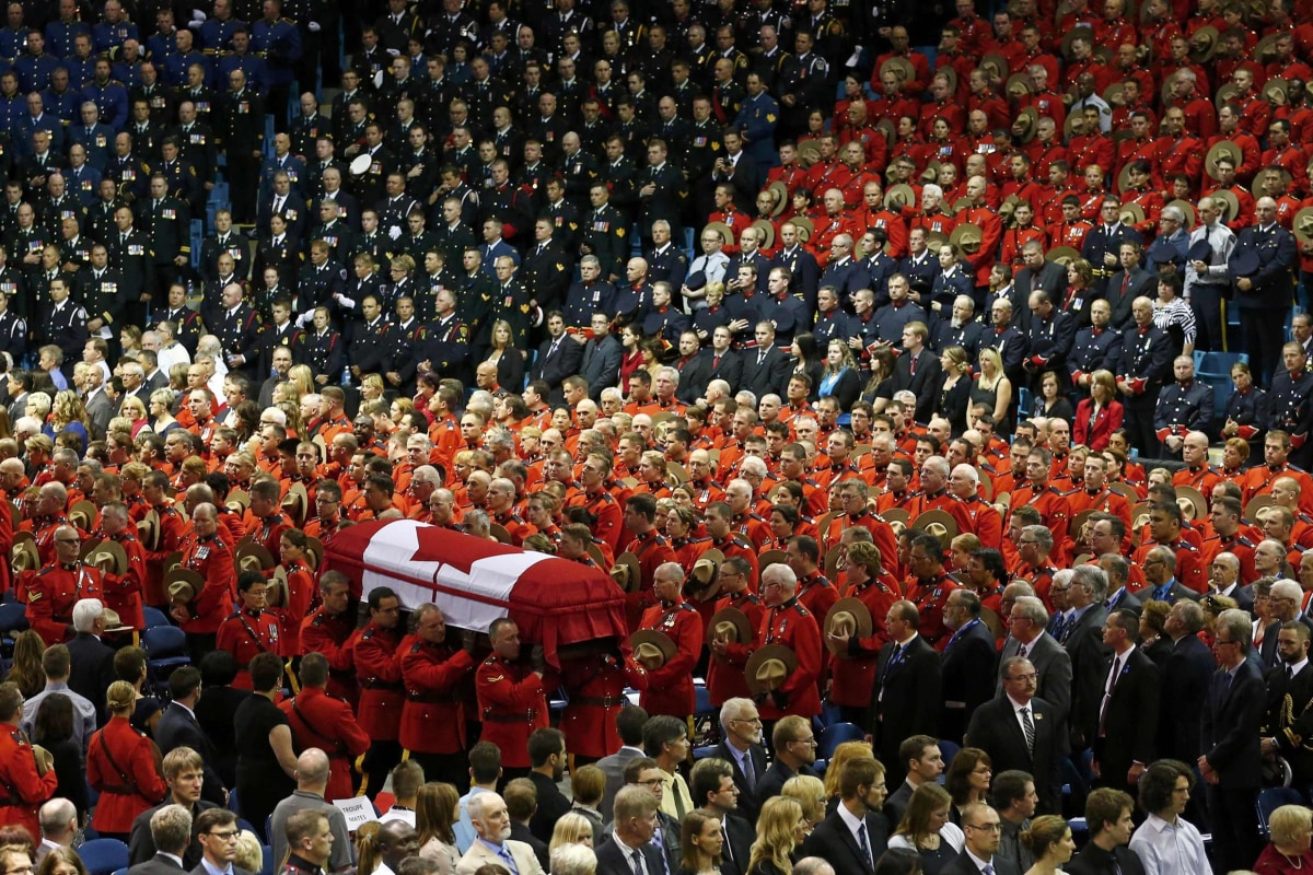 Image: Pallbearers carry the casket of one of three Royal Canadian Mounted Police officers who were killed last week during a regimental funeral in Moncton
