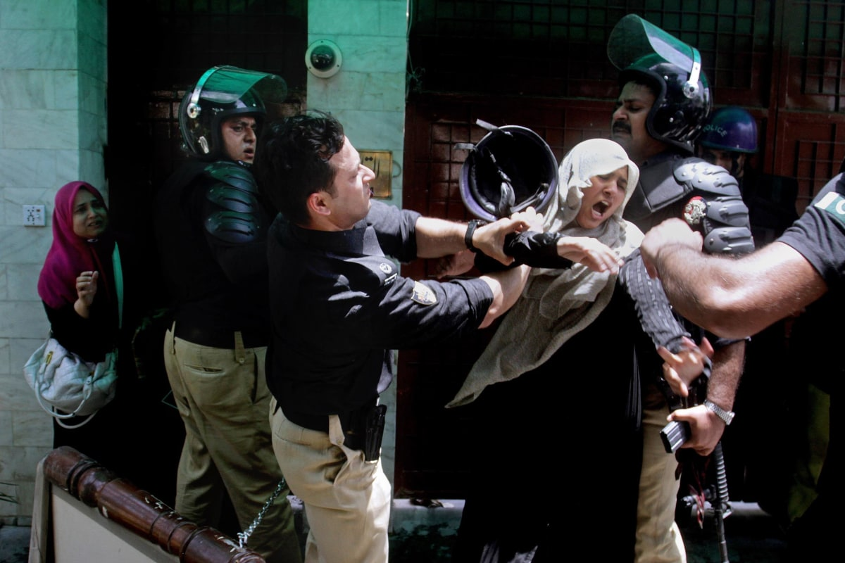Image: A Pakistani police officer scuffles with a female protester