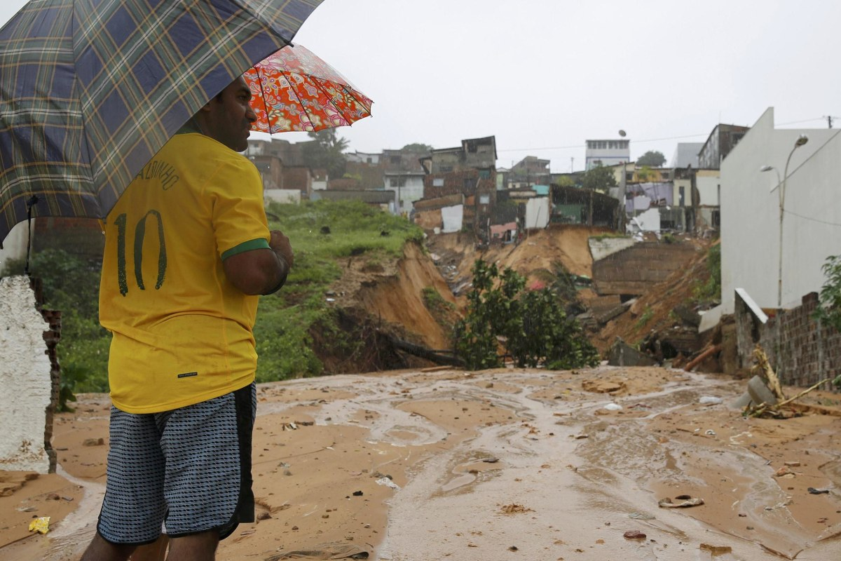Image: Man looks at the site of house destroyed by a landslide in Mae Luiza near Nata
