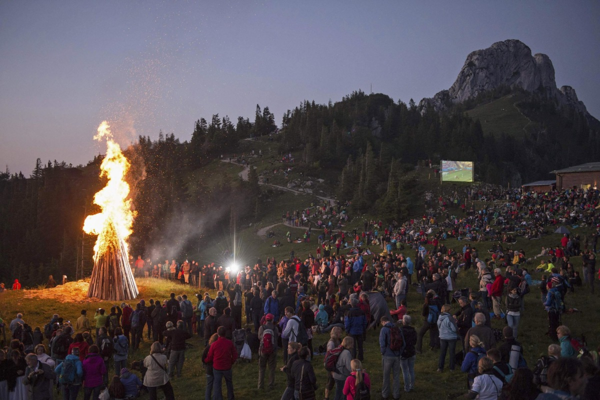 Image: People watch World Cup match between Germany and Ghana during the Sonnwendfeuer Festival at Mt. Kampenwand