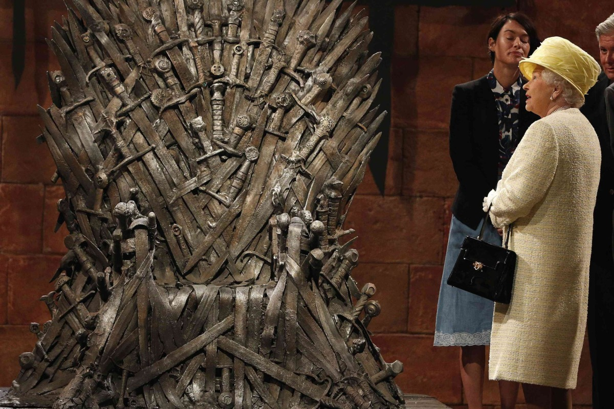 Image: Britain's Queen Elizabeth looks at the Iron Throne as she meets members of the cast on the set of the television show Game of Thrones in the Titanic Quarter of Belfast