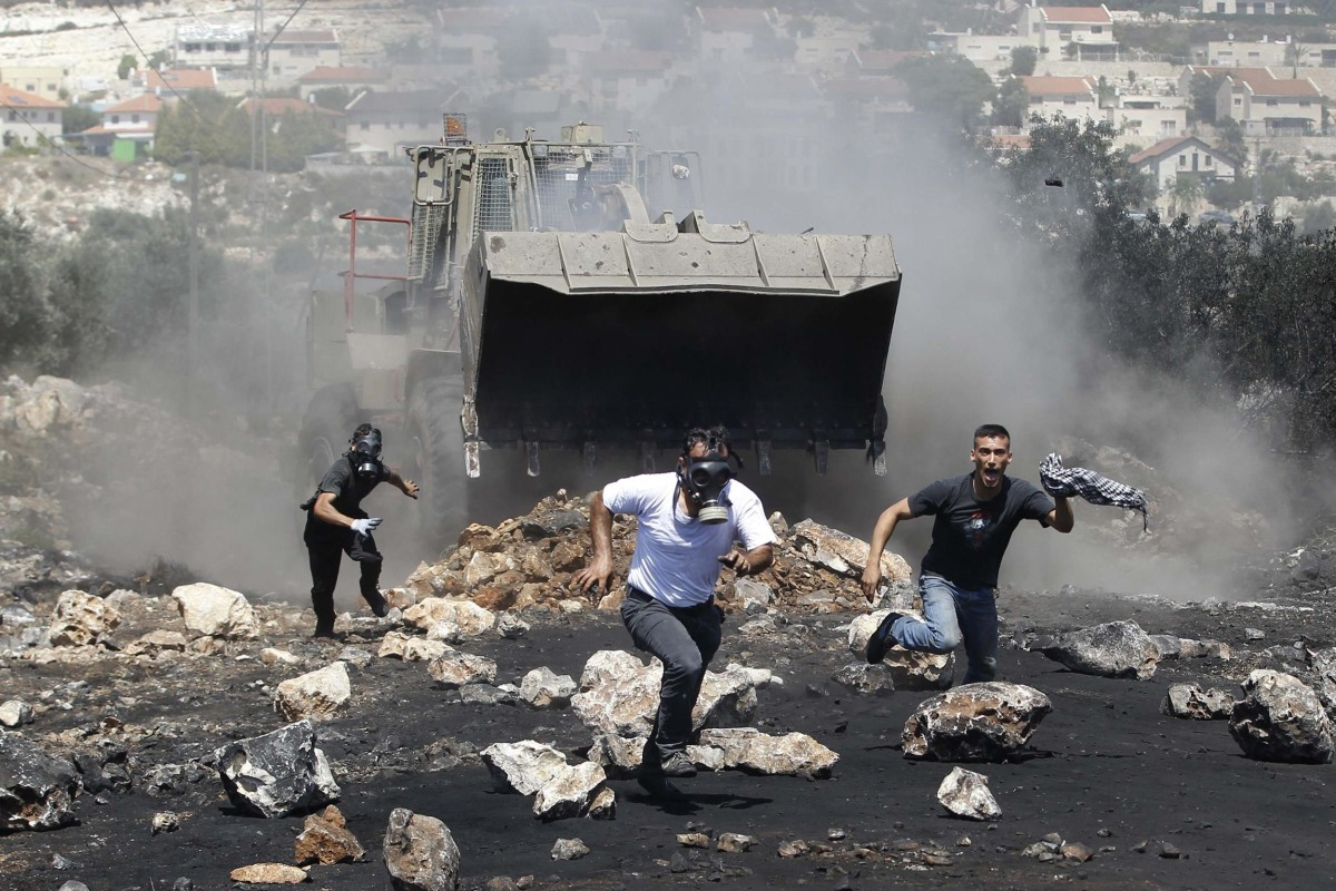 Image: Protesters run in front of an Israeli military bulldozer during clashes with Israeli troops following a protest against the nearby Jewish settlement of Qadomem, in the West Bank village of Kofr Qadom