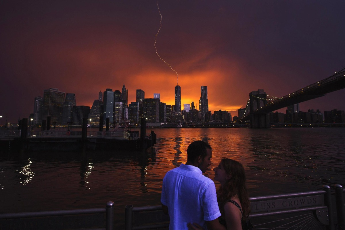 Image: A couple embraces as as lightning strikes One World Trade Center in Manhattan