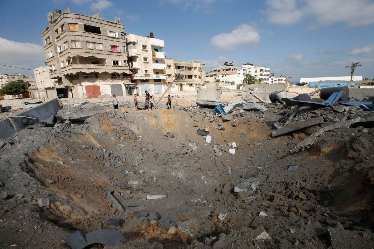 Image: Palestinians stand next to a crater which police said was caused by an Israeli air strike in Gaza City