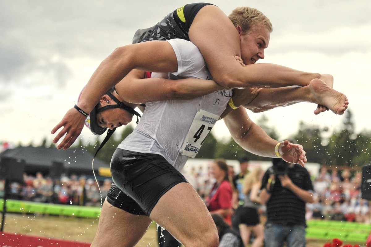 Image: Winning couple Ville Parviainen and Janette Oksman of Finland participate in the annual Wife Carrying World Championships in Sonkajaervi, Finland