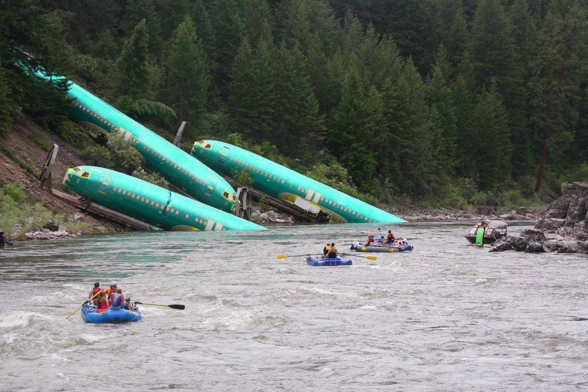 Image: Three Boeing 737 fuselages lie on an embankment on the Clark Fork River after a BNSF Railway Co train derailed near Rivulet