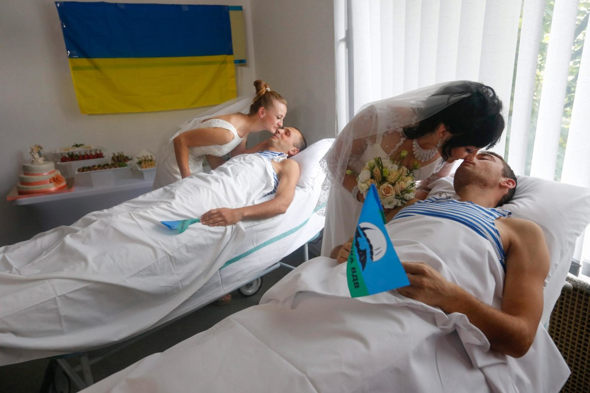 Image: Wounded members of the Ukrainian force kiss their brides in hospital beds