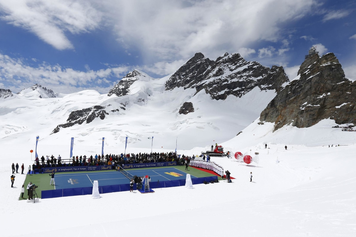 Image: Swiss tennis player Federer serves a ball to U.S. skier Vonn during a promotional tennis event on the Aletsch glacier at the Jungfraujoch