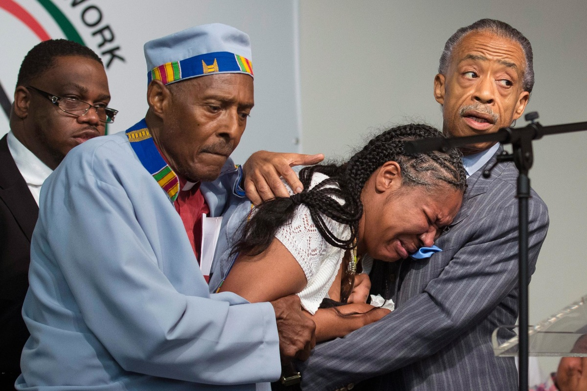 Image: Esaw Garner, center, wife of Eric Garner, breaks down in the arms of Rev. Herbert Daughtry and Rev. Al Sharpton