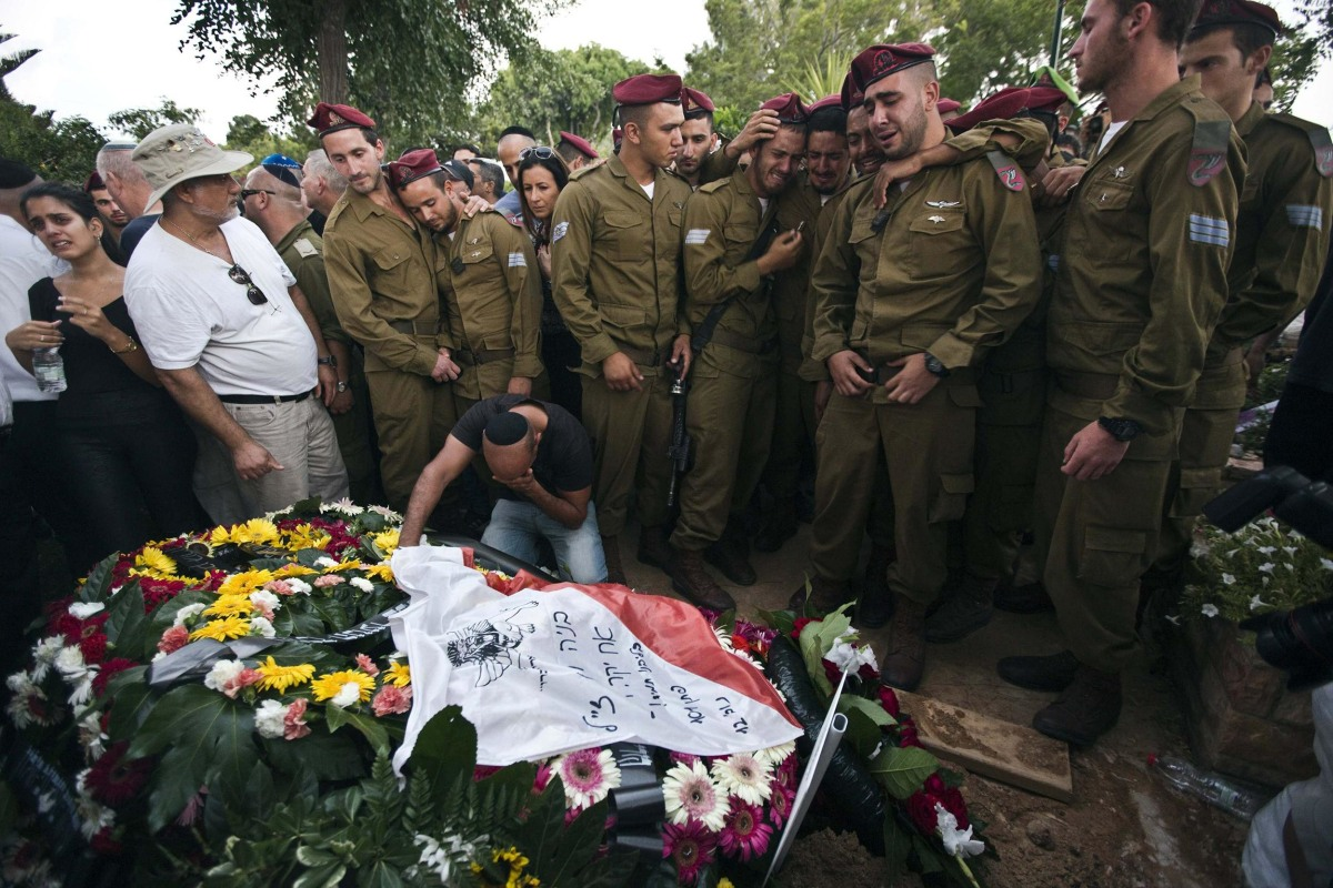Image: Israeli soldiers mourn with the brother of Israeli soldier Bnaya Rubel during Rubel's funeral in Holon