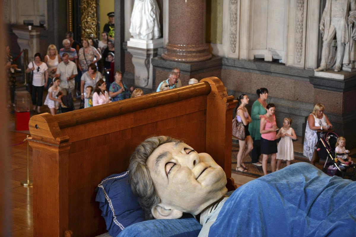 Image: Visitors look at a giant puppet of a grandmother sleeping on a bed inside St George's Hall in Liverpool