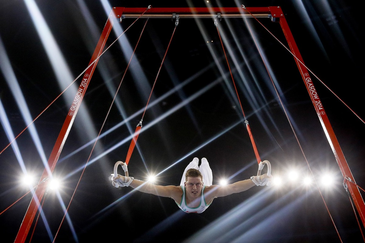 Image: Lights flare as Harry Owen of Wales performs on the rings during the Men's All-Around gymnastics competition